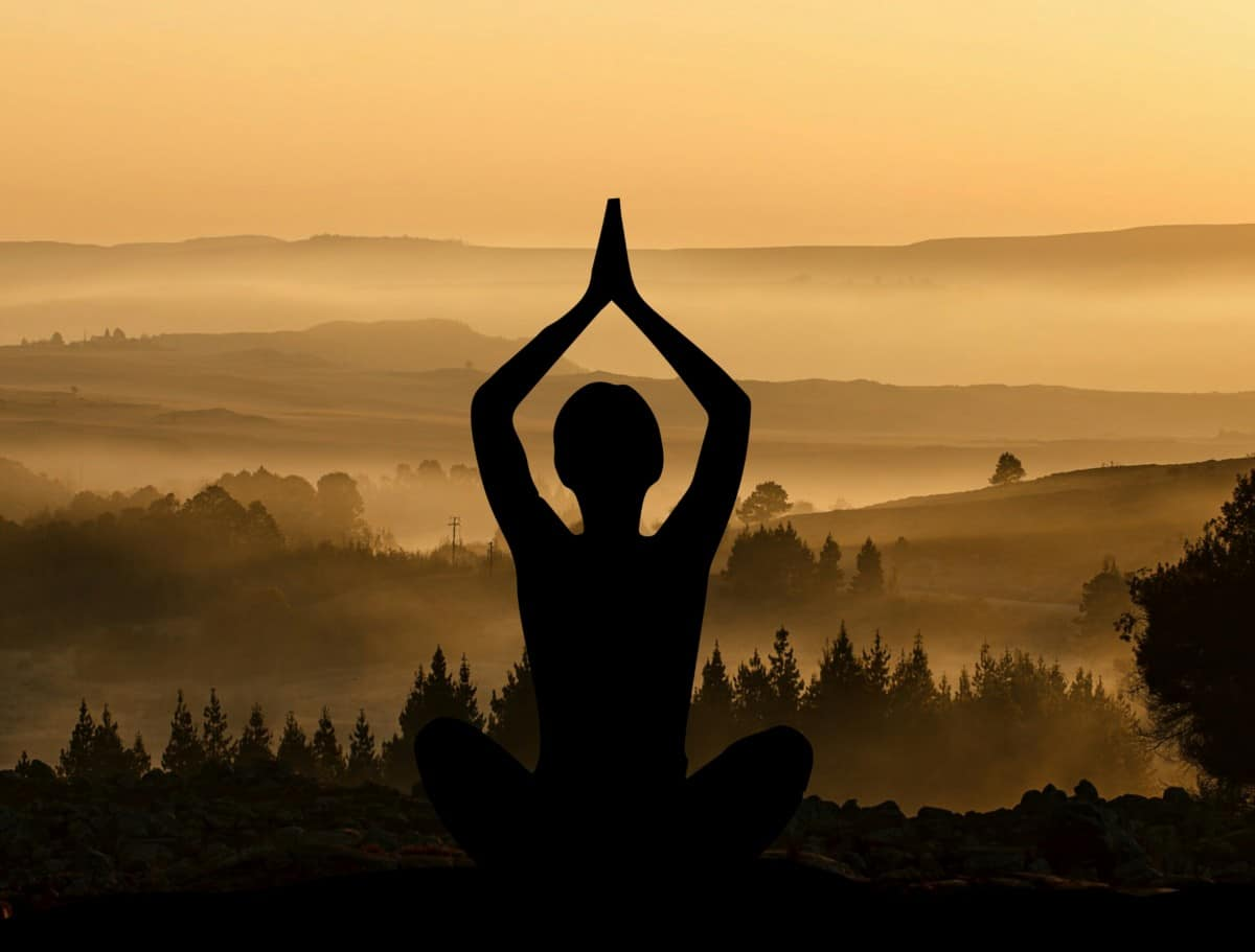 Woman in yoga pose with sunset peaceful