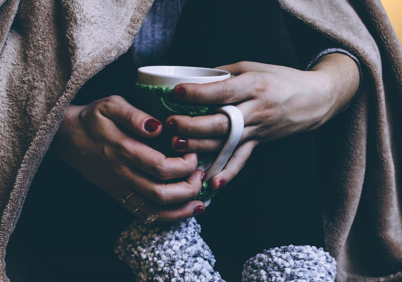 Woman with chronic pain holding a coffee cup and wrapped in a blanket.